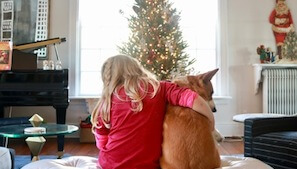 girl and dog in front of tree
